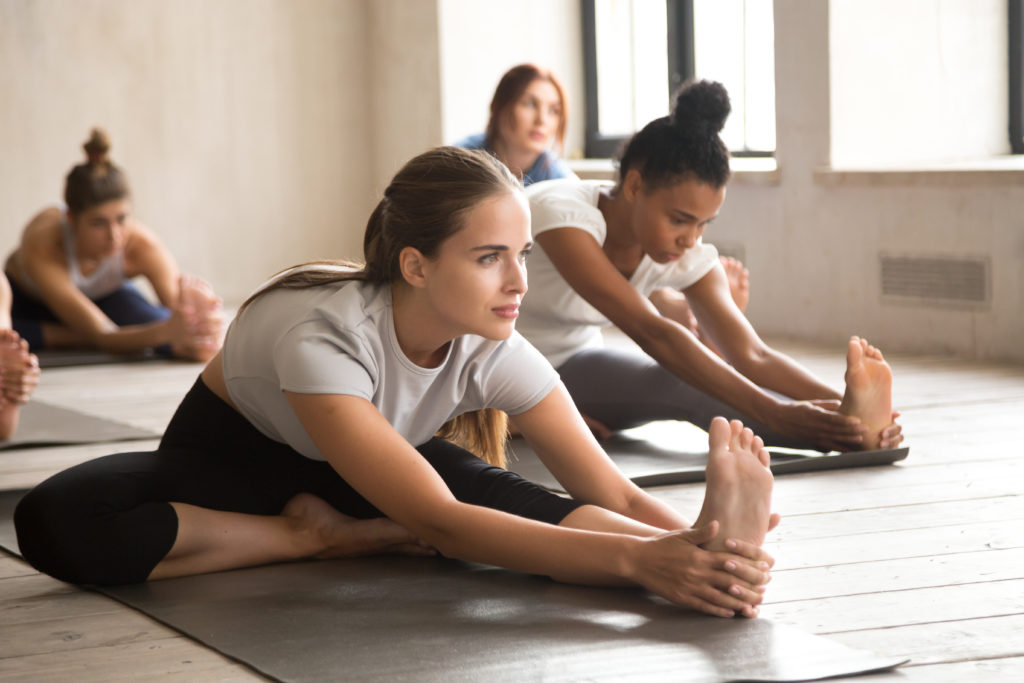 A group of people practicing a Head to knee forward bend exercise